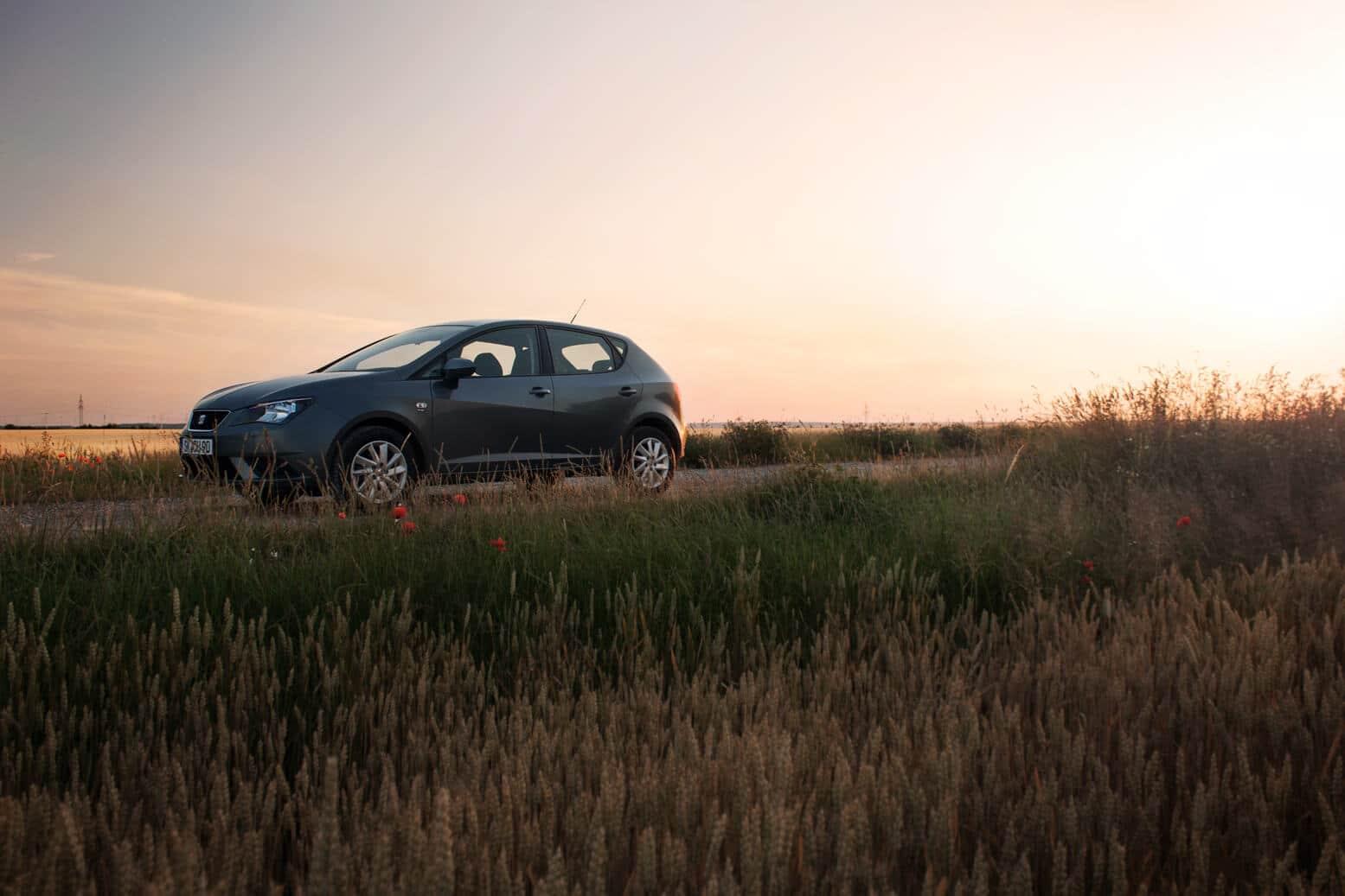 Seat Ibiza in grau an einem Feldweg bei Sonnenuntergang