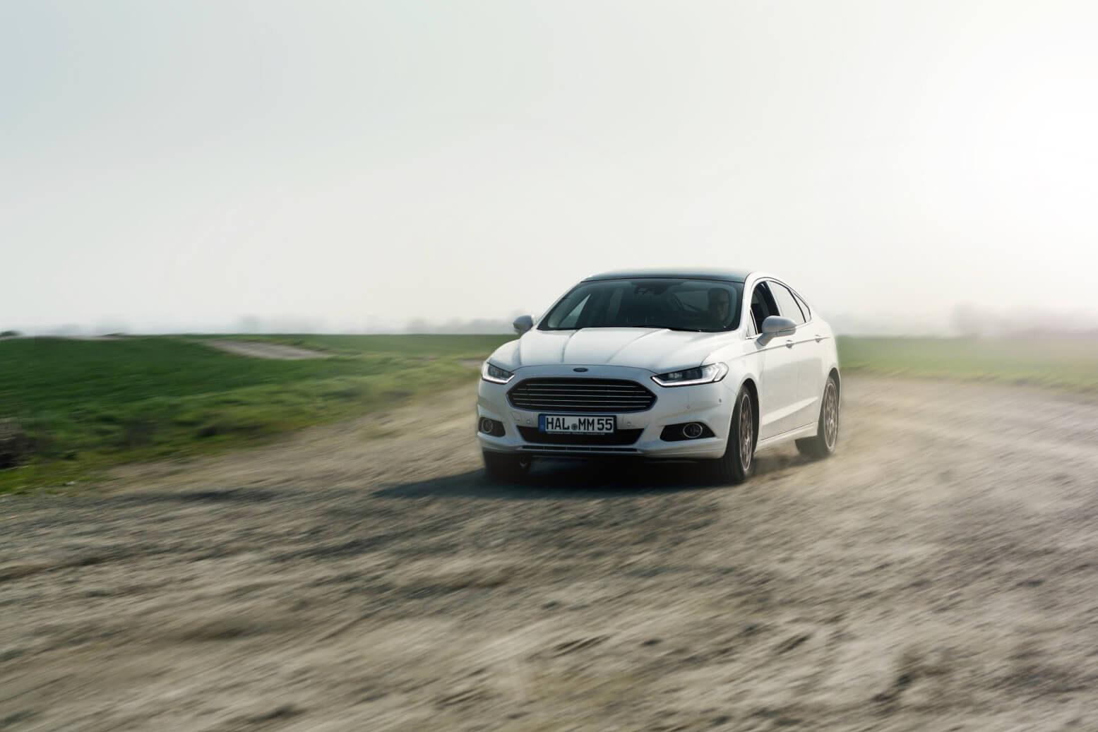 Ford Mondeo fährt um die Kurve auf einem Feldweg